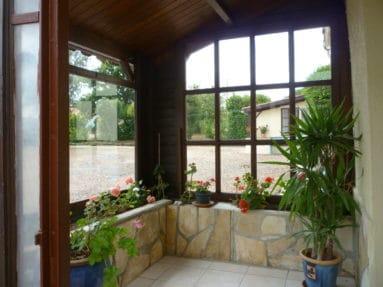 Kleine veranda aan de voorkant van Le Marronnier met bloeiende geraniums. La Petite Guyonnière fotografeert